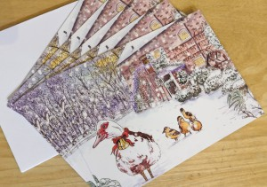 Five Christmas cards laid out in a fan. The card has an illustrated picture of The Watermill and some ducks in snow on the front.